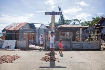 PHILIPPINES. Tagubanhan. Décembre 2013. Un pêcheur, dont le bateau a été détruit par le typhon Haiyan, attend à l'ombre d'une croix. THE PHILIPPINES. Tagubanhan. December 2013. A fisherman, whose boat was destroyed by typhoon Haiyan, is waiting in the shade of a cross.