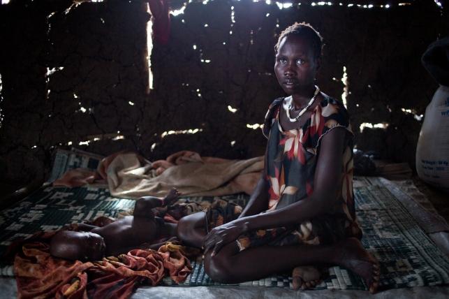 Leitchor, région de Gambella, Ethiopie. Nyuthing Jock Kheit et son fils de six mois ont fui la ville sud-soudanaise de Malakal en janvier. Ils vivent dans le camp de réfugiés de Leitchor. Juin 2014.