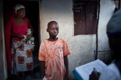 Monrovia, Libéria, novembre 2014. L'un des fils de Monsieur Diko répond aux questions de Stephen Kpoto, contact tracer dans le bidonville de West Point. Tous les matins, entre 6h30 et 8H30, les équipes de contact tracers visitent chacun entre 10 et 20 personnes ayant été en contact avec un malade d'Ebola, afin de vérifier qu'elles n'ont pas été contaminées par le virus.