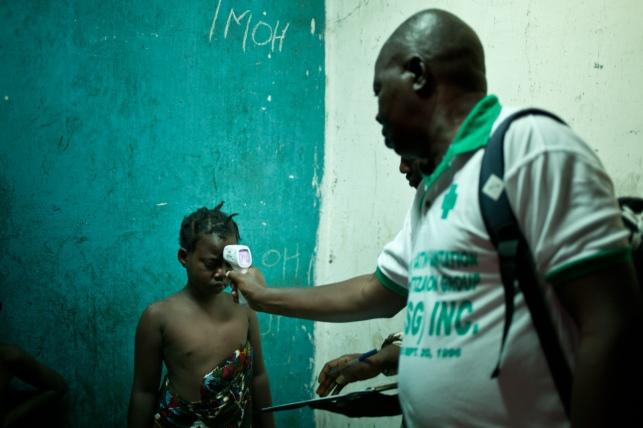 Monrovia, Libéria, décembre 2014. Un contact tracer de l'équipe de West Point vérifie que l'un de ses contacts n'a pas de fièvre.