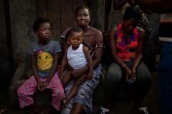 Monrovia, Libéria, novembre 2014. Au centre, Francis Jey, 1 an et huit mois. Lui et sa famille ont été en contact avec un malade d'Ebola. Le lundi 18 novembre, sa température est de 37,7 degrés. Une ambulance viendra le chercher plus tard pour l'emmener dans un centre de traitement Ebola afin de vérifier s'il s'agit ou non du virus. Bidonville de West Point.