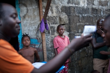 Monrovia, Libéria, novembre 2014. Un contact tracer de l'équipe de West Point vérifie que l'un de ses contacts n'a pas de fièvre.