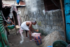 Monrovia, Libéria, novembre 2014. Un homme fait sa lessive pendant que les contact tracers questionnent ses voisins. Vendredi 28 novembre 2014, bidonville de West Point.