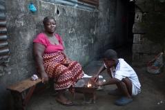 Monrovia, Libéria, novembre 2014. Une femme habitant dans le bidonville de West Point attend le passage des contact tracers. Sa fille est décédée après avoir contracté le virus Ebola.