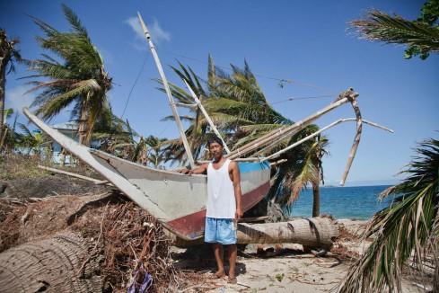 PHILIPPINES. Calagnaan. Décembre 2013. José Logronio Junior, 49 ans, pêcheur, devant son bateau détruit lors du passage du typhon Haiyan. THE PHILIPPINES. Calagnaan. December 2013. Jose Logronio Junior, 49, fisherman, in front of his boat destroyed by typhoon Haiyan.