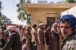 Camp d'Ain Issa, Syrie. File d'attente pour que les personnes souhaitant quitter le camp et continuer leur route obtiennent des papiers de transit.
