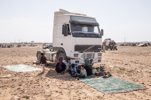 Camp d'Ain Issa, Syrie. Une famille s'abrite à l'ombre d'un camion, en attendant de recevoir une tente. En septembre 2017, 80 à 90% des nouveaux arrivants venaient de la région de Deir Ez-Zor.