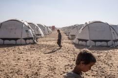 Camp d'Ain Issa, Syrie. Deux jeunes hommes marchent entre les rangées de tentes du camp d'Ain Issa.