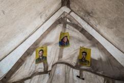 Camp d'Ain Issa, Syrie. Les photographies militaires des hommes de la famille d'Aziza, partis rejoindre les Forces Démocratiques Syriennes (FDS), une alliance kurdo-arabe soutenue par la coalition internationale, qui combattent le groupe Etat islamique. Aziza et sa famille habitaient la banlieue de Raqqa. Ils ont fui en mai dernier. Les combattants du groupe Etat islamique voulaient les obliger à rejoindre le centre-ville afin de se servir des civils comme boucliers humains. Les soldats de l'EI avaient creusé des trous dans les murs de sa maison, de manière à relier les immeubles entre eux afin de circuler à couvert. Son mari a rejoint les Forces Démocratiques Syriennes.