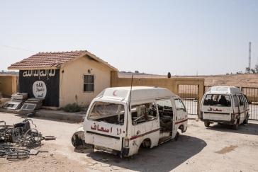 Tabqa, Syrie. Deux ambulances abandonnées sur le parking de l'hôpital de Tabqa. En second plan, le drapeau du groupe Etat islamique a été peint sur un mur. Tabqa a été reprise fin avril par les Forces Démocratiques Syriennes (FDS), une alliance de combattants kurdes et arabes soutenue par la coalition internationale. Lors des combats, les soldats du groupe Etat islamique se sont retranchés à l'intérieur de l'hôpital.