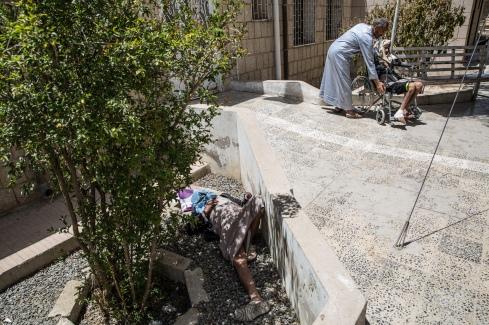 Yemen, gouvernorat d'Amran, Khamer, mars 2018. Un homme se repose à l'ombre d'un arbre tandis qu'un patient attend sa séance de physiothérapie, hôpital de Khamer.
