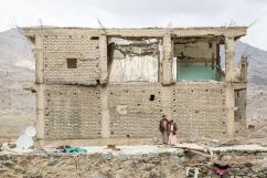 Yemen, gouvernorat de Saada, Haydan, mars 2018. Abdullah Ghani et son fils Salah posent devant leur maison, bombardée par l'aviation saoudienne pendant les guerres qui se sont tenues entre 2004 et 2010, opposant les Houthis aux forces armées menées par le président de l'époque, Ali Abdallah Saleh, assassiné en décembre 2017.