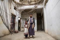 Yemen, gouvernorat de Saada, Haydan, mars 2018. Ayah (gauche) et Salah (droite) posent à l'intérieur de leur maison, bombardée par l'aviation saoudienne.