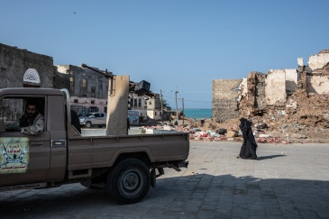 Yemen, Mocha, 10 December 2018 - Mocha downtown. A woman is walking near a non-standard tactical vehicle in Mocha city.